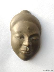 Face in bronze relief